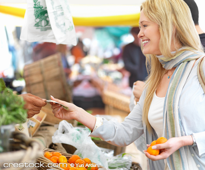 Happy beautiful blonde woman buying food at th...